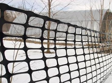 Black HDPE snow fence blocks snow on the road