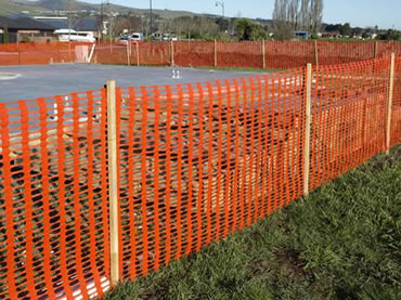Orange snow fence with wooden post encloses ground under construction