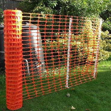 Orange temporary barrier fence installed with white steel stakes