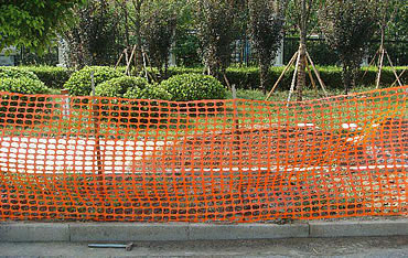 Orange temporary barrier fence protects roadbed