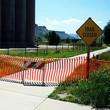 Orange temporary barrier fence with warning signal post - trail closed